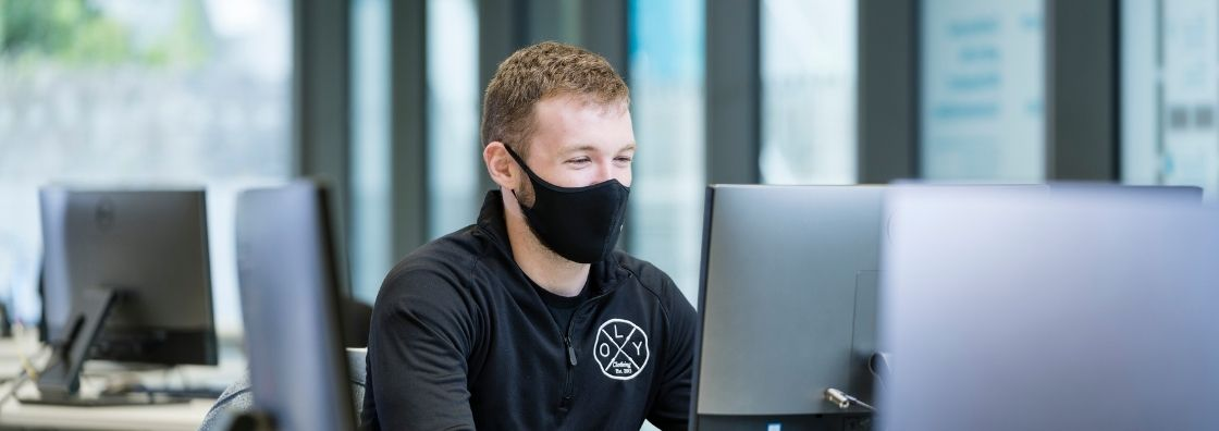 A student wearing a black face mask works at a computer in Maynooth University