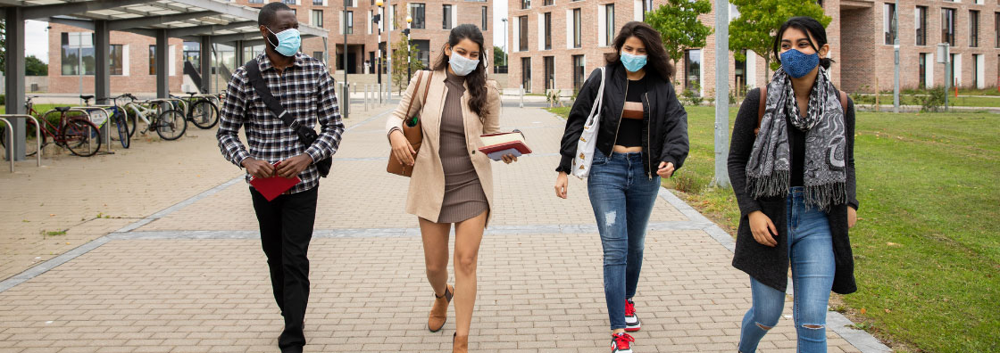 4 students, wearing masks, walk on the North Campus of Maynooth University