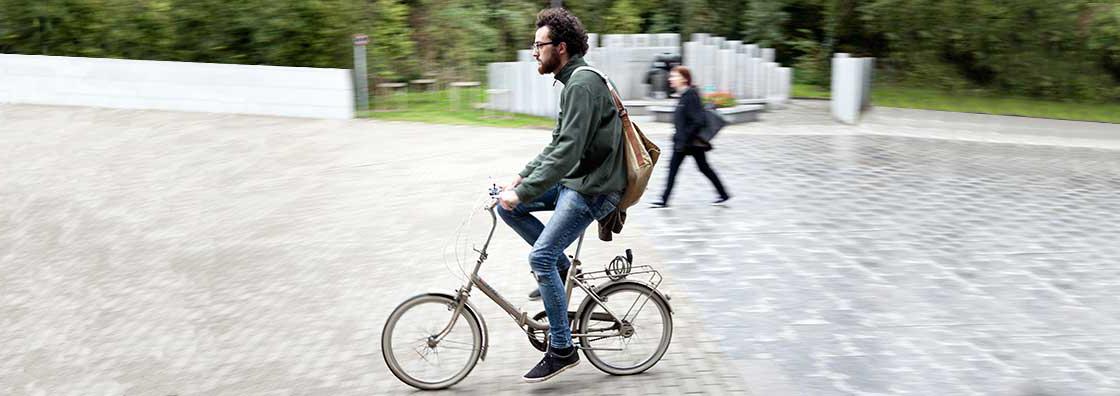 Communications & Marketing -  - Maynooth University Male on bike outside library motion blur 1120 x 396