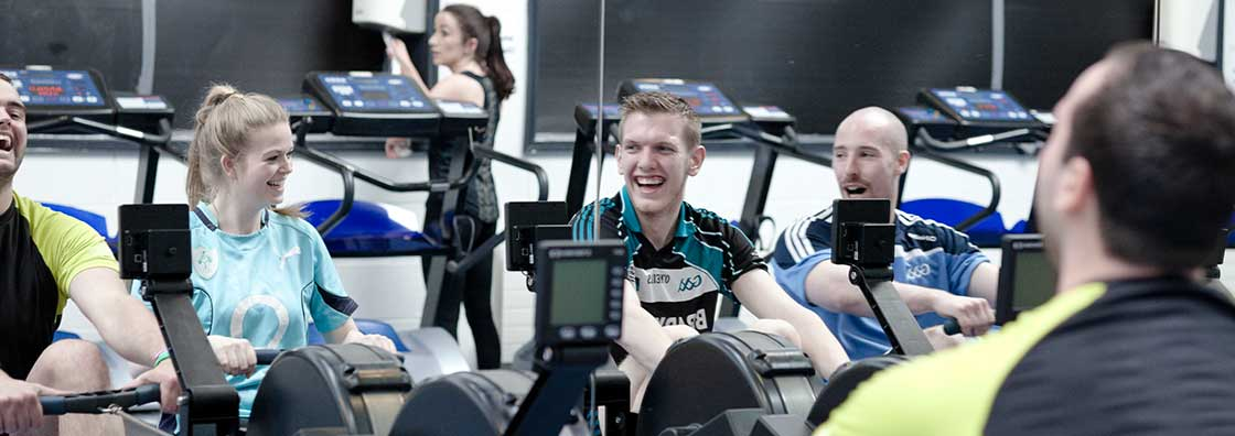 Student Services - Gym - students on rowing machines laughing - Maynooth University