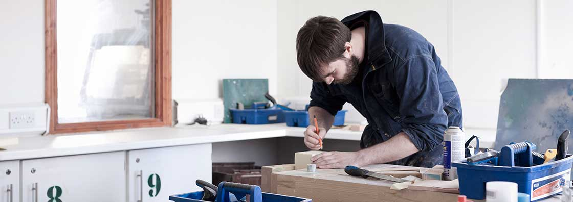 Design Innovation - student in overall in a workshop - Maynooth University