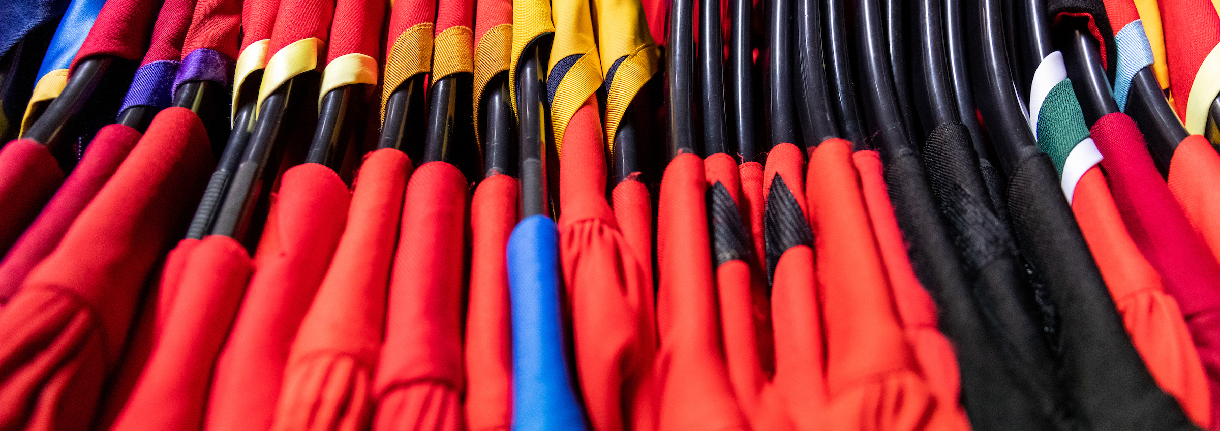 A line of doctoral robes for conferring, hanging up on black hanges