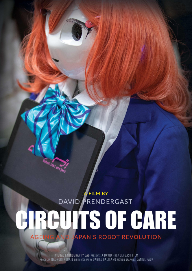 Text: Film by David Prendergast: Circuits of Care Ageing and Japan's Robot Revolution. Image in Background robot dressed in female clothing - blue suit white blouse and light blue cravat with a red wig holding an interactive tablet