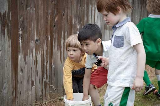 Creche - Children dipping in bucket - Maynooth University