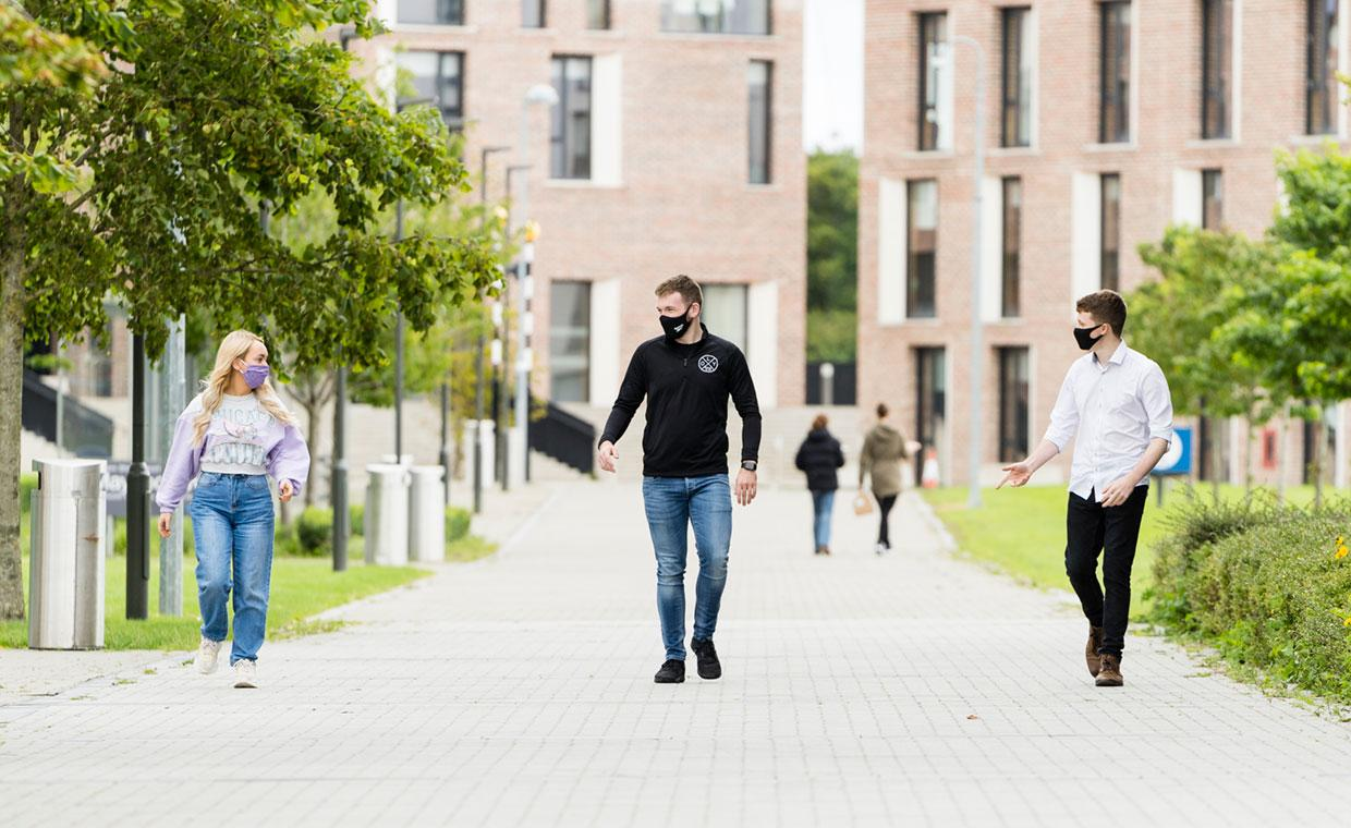 Three students wearing masks walk with 2 metres between them, the new residence building on the North Campus is behind them