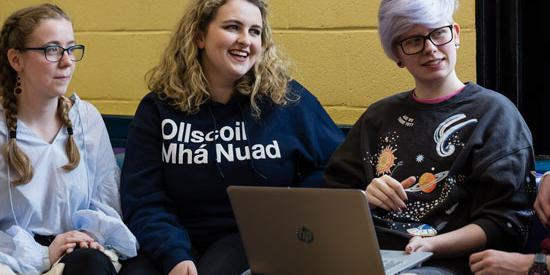 3 students sitting around a laptop.  One wears a sweater with 'OllScoil Mhá Nuad'