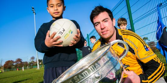 Student Union's meet your GAA heroes day - Michael Darragh MacAuley with a young pupil and the Sam Maguire Trophy