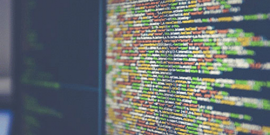 Multi-coloured lines of code: yellow, red, green and white, on a screen