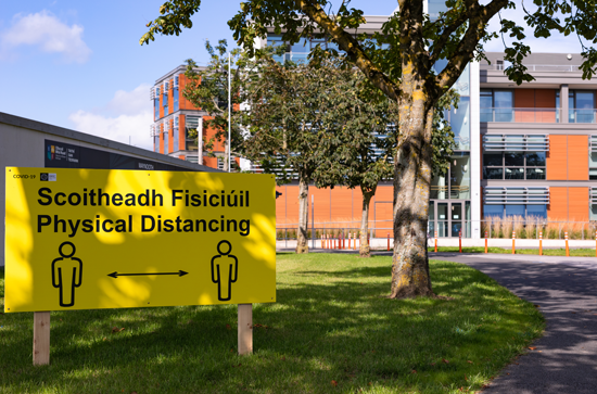 A yellow and black physical distancing sign on the path between the Education Building and the Kilcock Road