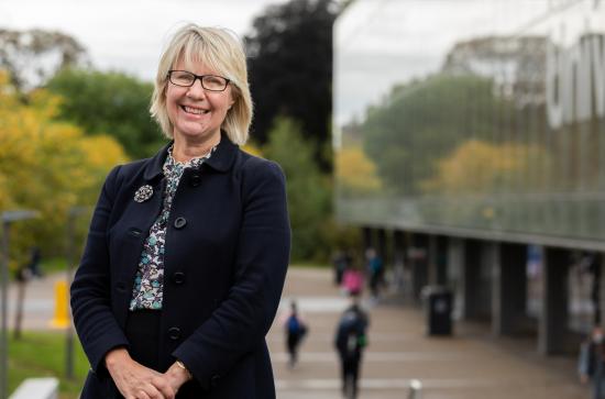Professor Eeva Leinonen in a dark blazer stands in front of MU Library